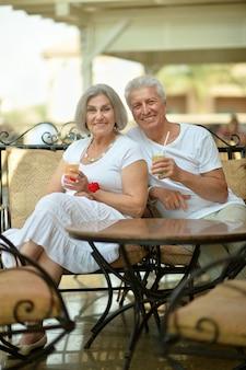 カフェでジュースを飲んで幸せな笑顔の老夫婦をおもしろい