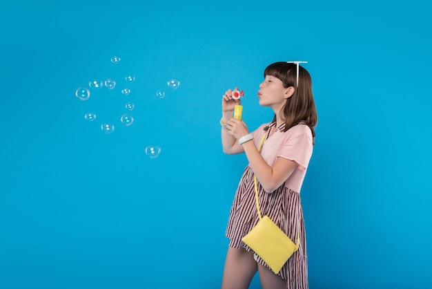 Amusing. inspired lovely girl wearing stylish clothes and blowing soap bubbles
