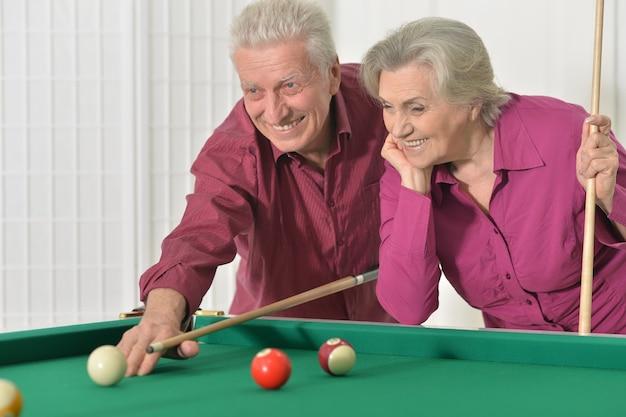 ビリヤードをする休暇でおもしろい老夫婦