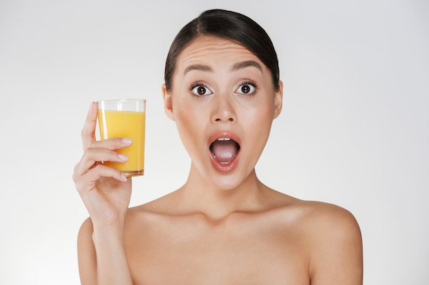 Amusing photo of funny woman with dark hair in bun holding transparent glass of fresh-squeezed orange juice, isolated over white wall