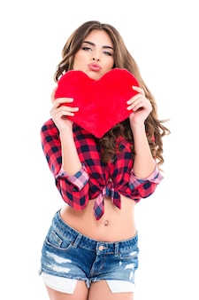 Amusing pretty young woman in casual clothes holding red heart and making funny duck face over white wall