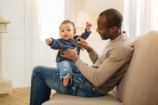 Amusing son. good-looking happy afro-american man smiling and amusing his son while child is sitting on his lap