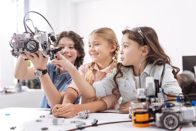 Забавно с нашим электронным другом. позитивные счастливые радостные ученики сидят в школе и играют с роботом во время работы над техническим проектом