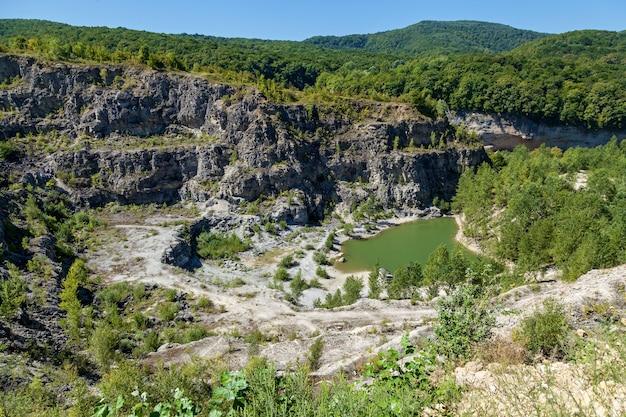 바닥에 녹색 호수가 있는 나무로 자란 버려진 화강암 채석장. 아디게아의 자연과 풍경