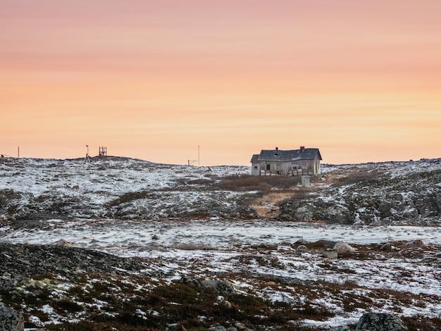 放棄された気象ステーション。岩の多い海岸にある古い老朽化した家のある夕方の極地の風景。冬のテリベルカ。