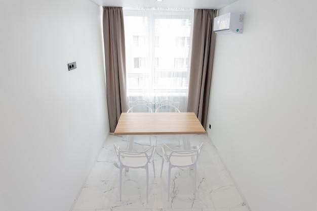 창가 의자 옆에 식탁이 있는 밝은 색상의 절대적으로 멋진 주방 인테리어