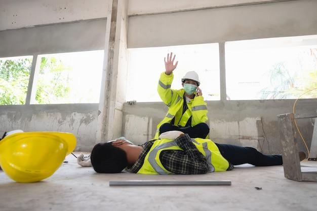 건설 현장에서 남성 작업자의 사고와 구조 및 인명 구조를 위해 안전 담당자를 호출합니다. 부상당한 사람에 대한 선택 초점.