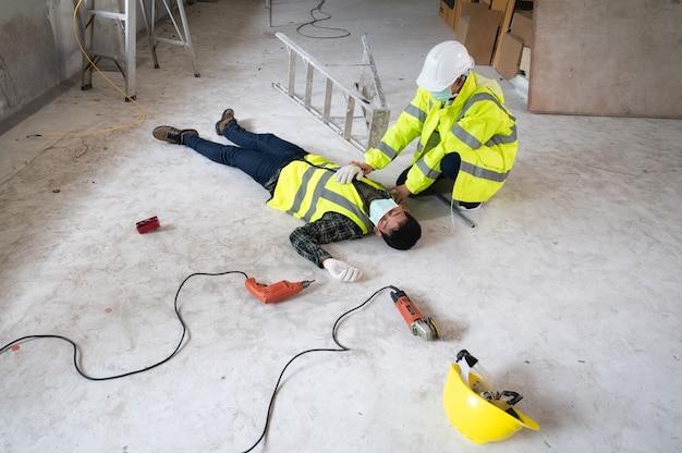 건설 현장에서 남자 노동자의 사고. 프라이머리에서 부상당한 사람들을 돕습니다. 부상당한 사람에 대한 선택 초점.