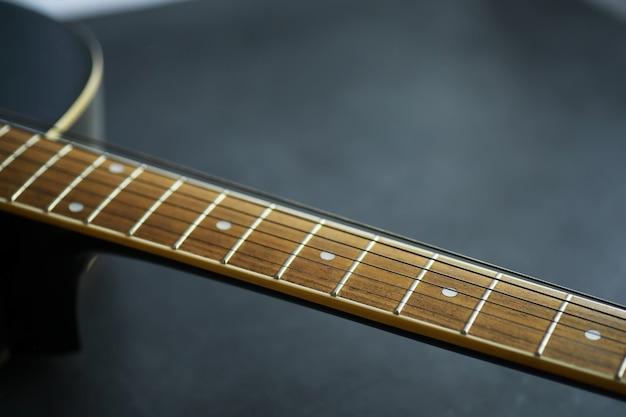 무대에서 현악기를 연주하는 아티스트를 위한 어쿠스틱 기타. 카포가 달린 검은색 기타. 음악적 배경입니다.