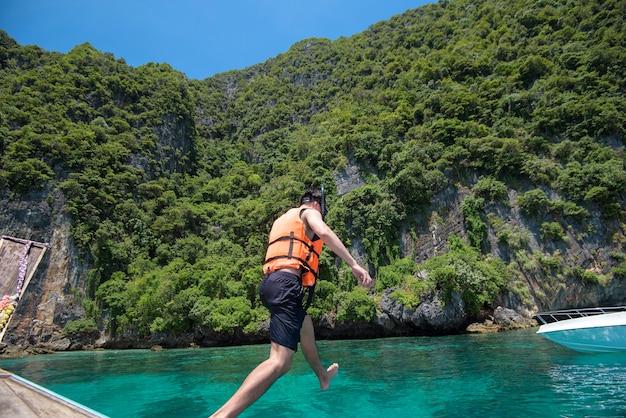 태국 전통 롱테일 보트에 적극적인 남자가 스노클링과 다이빙을 할 준비가되었습니다, 피피섬, 태국