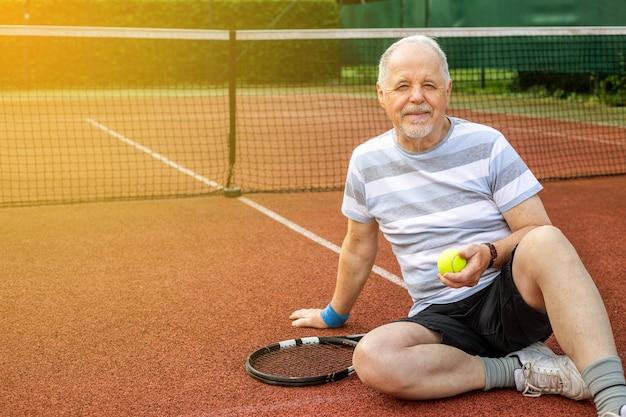사랑스러운 여름날을 즐기고 밖에서 테니스를 치는 활동적인 연금 수급자 남자