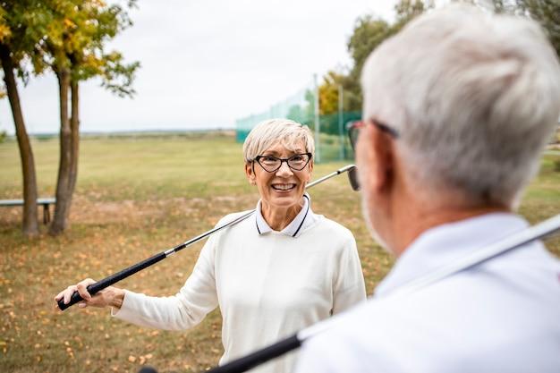 Активная пара пожилых людей с гольф-клубами, проводящая свободное время на открытом воздухе.
