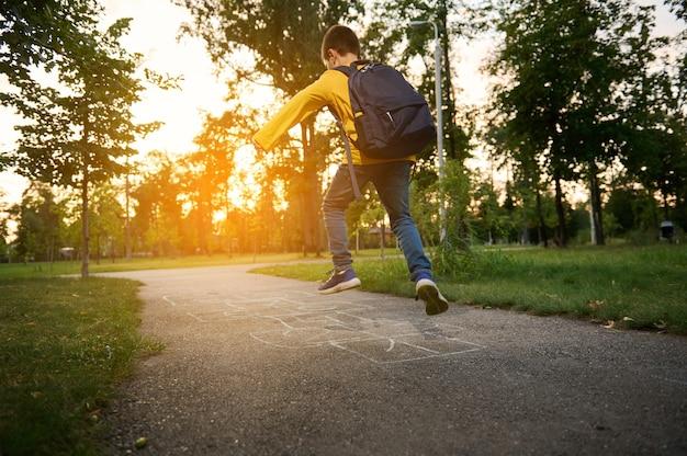 ランドセルを背負ったアクティブなスポーティな男の子は、放課後、石けり遊びをし、地面にマークされた正方形を交互に飛び越えます。クラシックのストリートチルドレンゲーム。