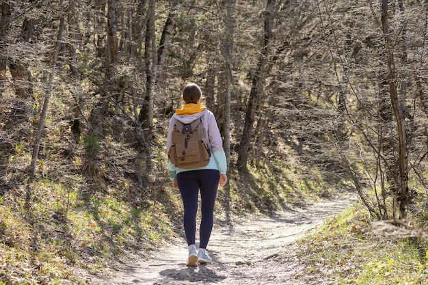 大きなハイキングバックパックを持ったアクティブな女性旅行者が木々の間の森を歩きます