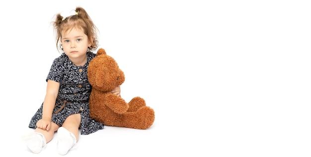 큰 황갈색 테디 베어를 만족스럽게 안고있는 사랑스러운 2 살 소녀