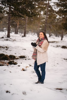 Очаровательная и расслабленная женщина в пальто позирует во время снегопада