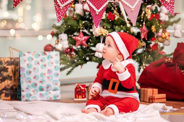 サンタクロースに扮した愛らしい男の子が、リビングルームの飾られたクリスマスツリーの近くで遊んでいます。
