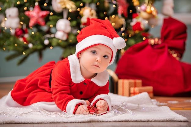 サンタクロースに扮した愛らしい子供が、リビングルームの飾られたクリスマスツリーの近くで遊んでいます。
