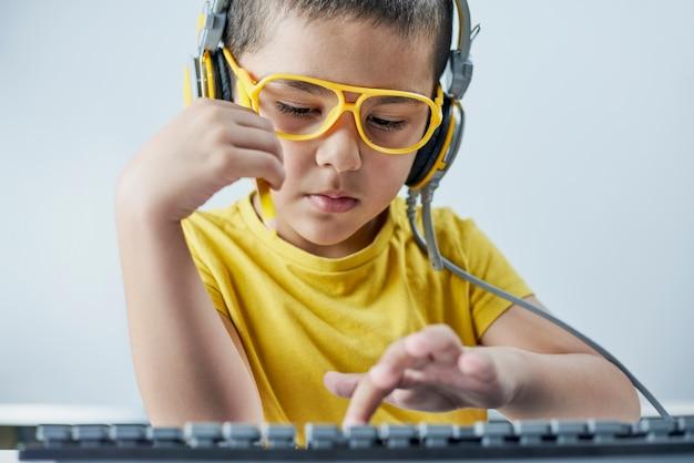 온라인 과정을 듣는 헤드폰이 달린 노란색 티셔츠를 입은 사랑스러운 아이.