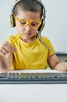 黄色のtシャツを着た愛らしい子供。ヘッドフォンで聞くオンラインコース。