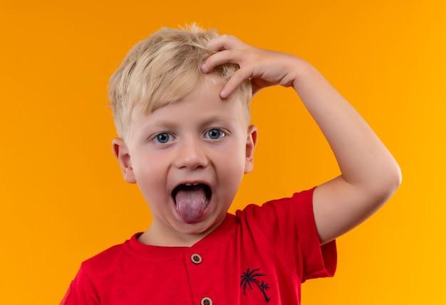 Очаровательный маленький мальчик со светлыми волосами и голубыми глазами в красной футболке, держащий руку за голову с открытым ртом