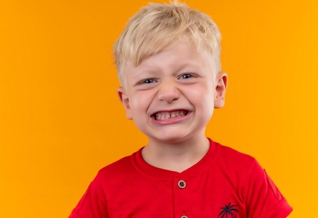 그의 이빨을 보여주는 빨간 티셔츠를 입고 금발 머리와 파란 눈을 가진 사랑스러운 작은 소년