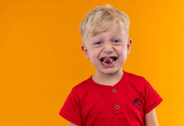 금발 머리와 그의 혀를 보여주는 빨간 티셔츠를 입고 파란 눈을 가진 사랑스러운 작은 소년