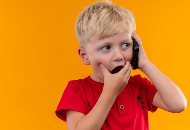 Очаровательный маленький мальчик со светлыми волосами и голубыми глазами в красной футболке разговаривает по мобильному телефону, удивительно глядя сбоку, положив руку на рот