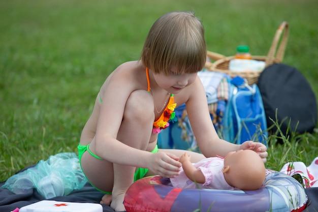 公園の芝生でピクニックをしているときに、明るい水着を着た愛らしい少女がお気に入りの人形と遊ぶ
