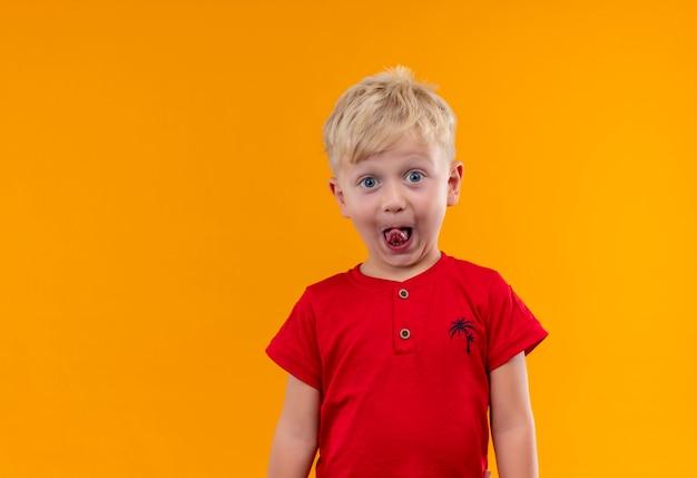 금발 머리와 그의 혀를 보여주는 빨간 티셔츠를 입고 파란 눈을 가진 사랑스러운 웃는 어린 소년