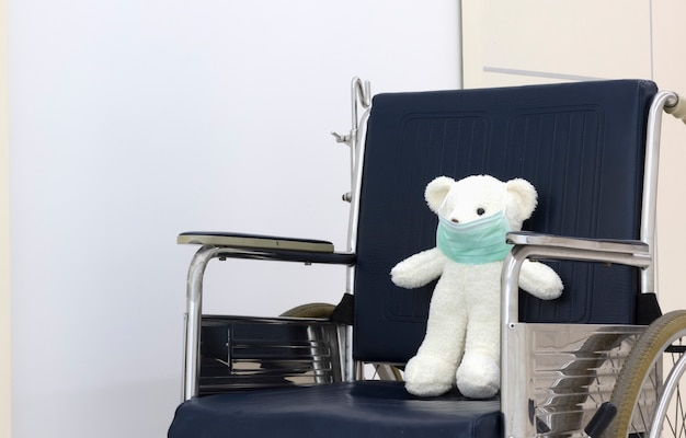 Очаровательный плюшевый мишка с маской для лица стоит на инвалидной коляске