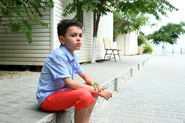 Очаровательный мальчик-подросток сидит на каменной ступеньке у морского коттеджа. красивый парень под открытым небом наслаждается отпуском. деревенские каникулы школьников. летняя концепция