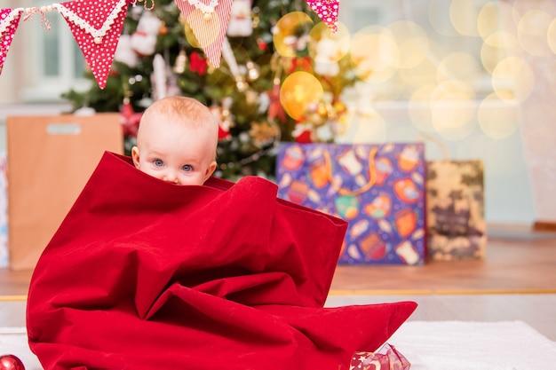 サンタに扮した愛らしい幼児が、クリスマスツリーのある装飾されたリビングルームでサンタクロースのクリスマス袋から覗きます。