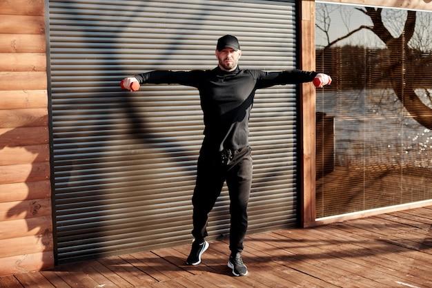 Взрослый спортивный человек выполняет упражнения с гантелями. мужчина занимается спортом на открытом воздухе как часть здорового образа жизни