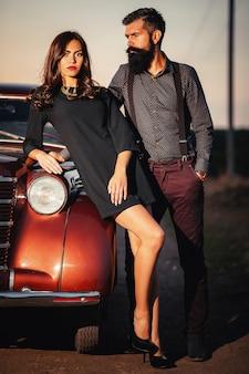 シャツとサスペンダーのズボンを着た大人のひげを生やしたブルネットの男は、暗いフィールドの背景に茶色のレトロな車の近くにある黒い短いドレスを着た長い髪の細い若い女の子を抱きしめます