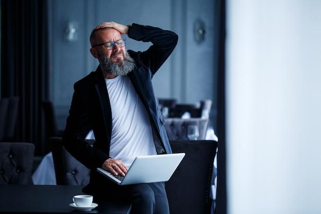 안경에 수염을 기른 성인 사업가가 노트북을 무릎에 올려 놓고 일합니다. 감독이 워크플로 일정을 수립합니다.