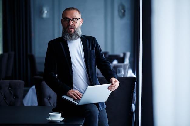Взрослый бизнесмен с бородой в очках сидит с ноутбуком на коленях и работает. менеджер составляет график рабочего процесса