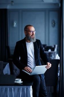 안경에 수염을 기른 성인 사업가가 노트북을 무릎에 올려 놓고 일합니다. 관리자가 워크플로 일정을 작성합니다.