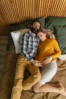 子供を待っている恋の大人のカップル。男と彼の妊娠中の妻は寝室のベッドで日光浴をしている