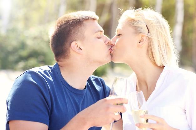 Взрослая пара целуется на пляже с бокалами шампанского