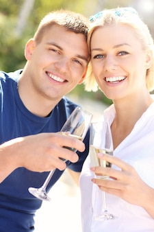 Взрослая пара с бокалами шампанского на пляже
