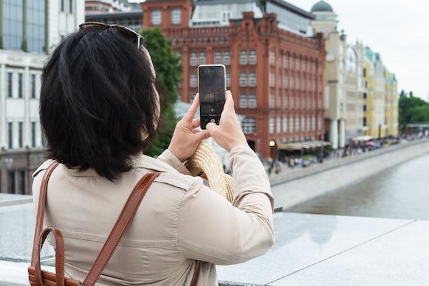 大人の黒髪の女性が旅行中に携帯電話でランドマークの写真を撮ります。
