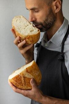 大人のヨーロッパの男性のパン屋は彼の手で丸い焼きたてのパンを持っていますパン屋の男性は