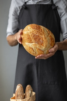 大人のヨーロッパ人男性のパン屋は、パン屋のイーストフリーの男性を手に丸い焼きたてのパンを持っています