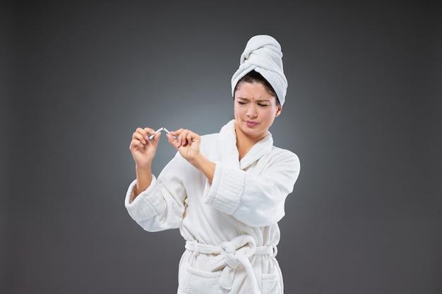 목욕 가운과 수건을 머리에 감은 성인 여성이 담배를 반으로 나누고 건강한 습관으로 바뀝니다.