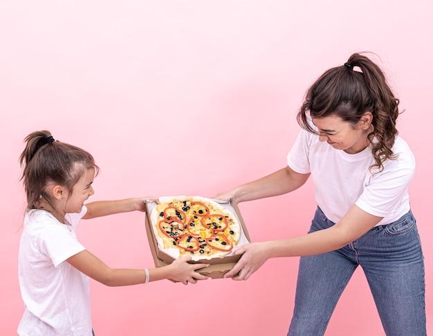 Взрослая девочка и маленькая девочка не могут делить пиццу между собой.