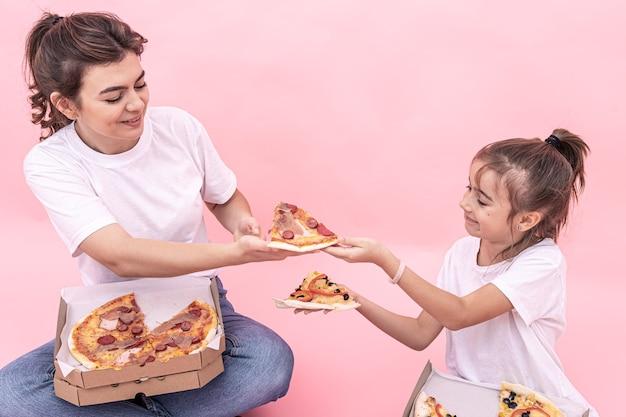 Взрослая девочка и маленькая девочка с разными пиццами в коробках, розовый фон.