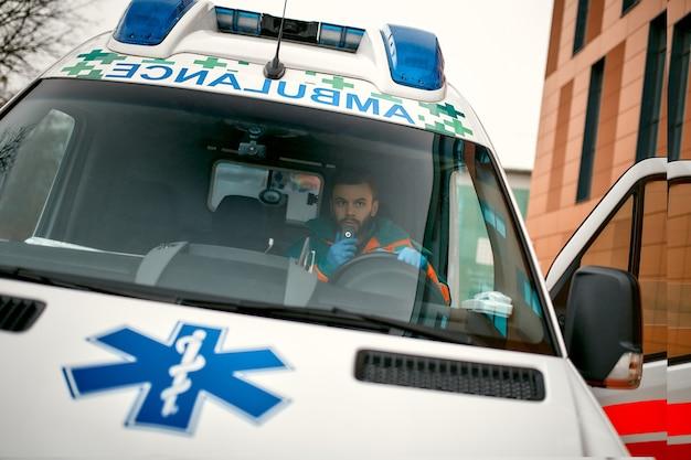 大人のハンサムな男性救急隊員が診療所の外の救急車に座っている間、携帯ラジオで話している。