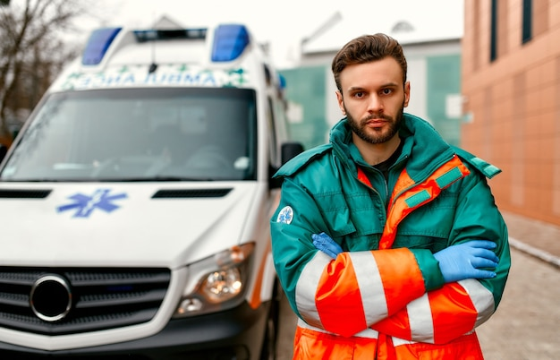 クリニック近くの救急車の前で腕を組んで立っている大人のハンサムな男性救急隊員。