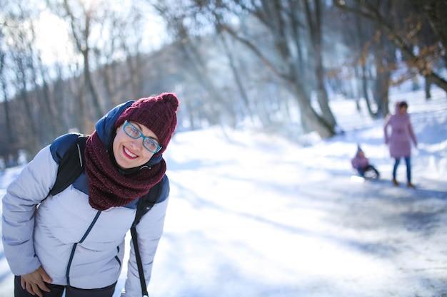 Взрослый в теплой зимней одежде веселится и смеется на улице во время зимней прогулки
